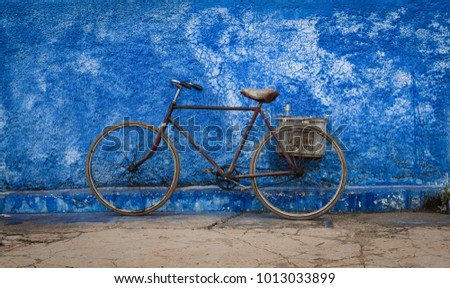 Old bicyle leading on a blue wall #1013033899