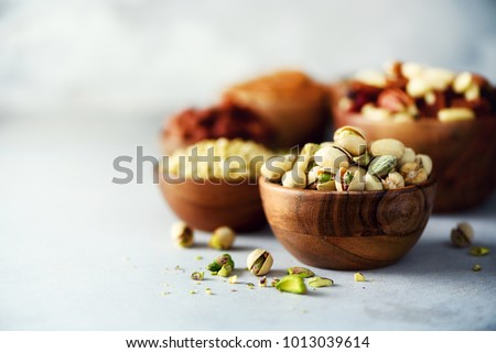Pistachios nuts in wooden bowl. Food mix background, top view, copy space, banner. Assortment of nuts - cashew, hazelnuts, almonds, walnuts, pistachio, pecans, pine nuts, peanut, raisins. Royalty-Free Stock Photo #1013039614