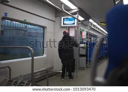 Russia, Moscow January 07, 2018. MCC in the wagon, near Kutuzovskiy prospect,  the person is looking at the scheme. City, architecture, transport, new technologies, modern wagon, handrails #1013093470