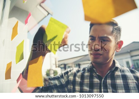 Young businessman reading sticky notes on the glass wall in office. Planning concept. #1013097550