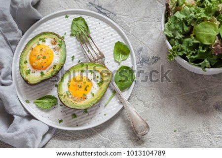 Healthy breakfast. Avocado stuffed with eggs on the table #1013104789