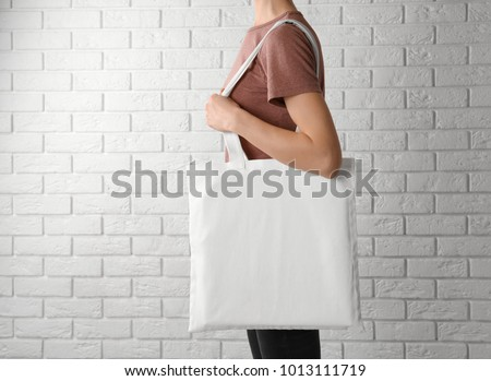 Woman with cotton bag near white brick wall. Mockup for design #1013111719