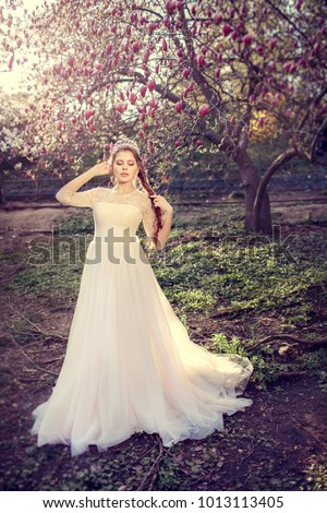 Beautiful bride posing near magnolia tree. Woman in white dress in spring garden. #1013113405