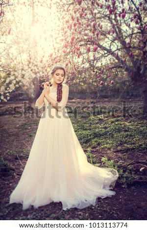 Beautiful bride posing near magnolia tree. Woman in white dress in spring garden. #1013113774