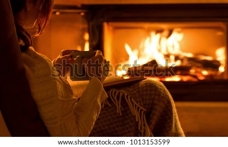 Young woman  sitting at home by the fireplace and reading a book. #1013153599