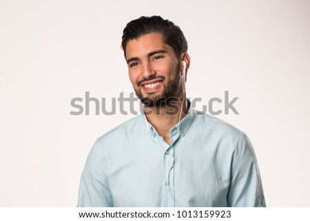 young man with earphones smiling  #1013159923