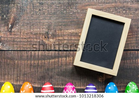Black picture in wooden frame and colorful easter eggs