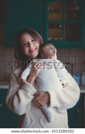 Young mother in sweater holding child indoor at kitchen.  #1013280583