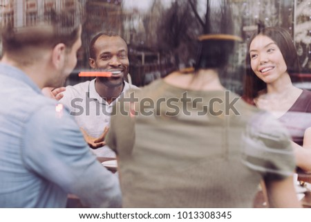 Nice day. Happy pleased four friends grinning while chatting and enjoying company #1013308345