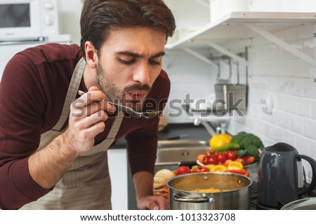 Young man cooking romantic dinner at home taste soup #1013323708