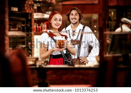 Young two people in bavarian clothes and their own small business of bar.  #1013376253