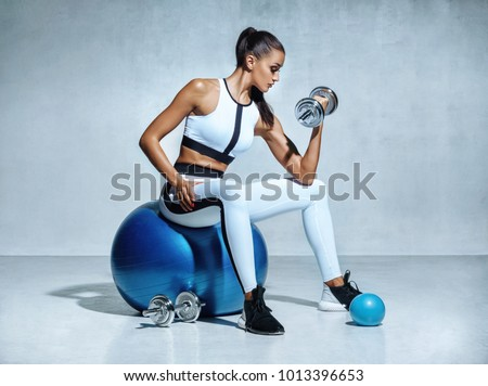 Strong woman working out with dumbbells sitting on gymnastic ball. Photo of sporty latin woman in sportswear on grey background. Sports #1013396653