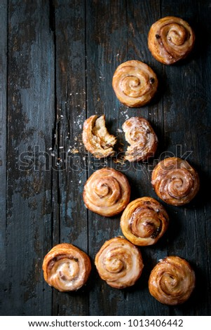 Homemade glazed puff pastry cinnamon rolls with custard and raisins over old dark blue wooden background. Top view, space. Rustic style #1013406442