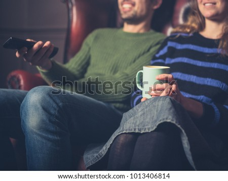A happy young couple on a sofa are watching television #1013406814