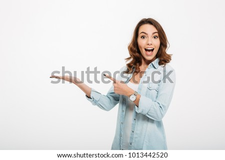 Photo of happy young woman standing isolated over white wall background. Looking camera showing copyspace pointing.