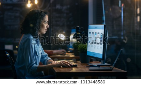 Beautiful Female Coder Works at Her Desktop on Her Peropnal Computer. Her Male Colleague Sits Next To Her. Evening Office Has Creative Lighting. #1013448580
