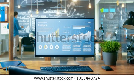 Personal Computer with Mobile Application Design Showing on the Monitor Stands on the Office Desk, In the Background Man Working in the Daytime Office Environment. Royalty-Free Stock Photo #1013448724