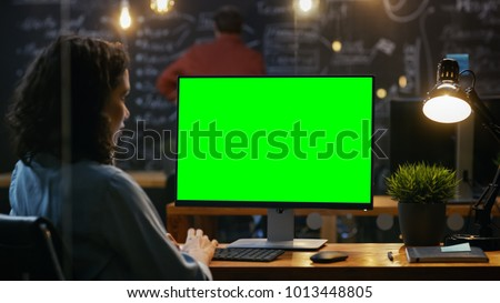 Beautiful Female Office Employee at Her Desktop Works on a Mock-up Green Screen Personal Computer. Over the Shoulder Footage. Her Colleague works in the Background. Creative Office Evening. #1013448805
