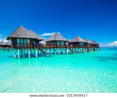 Maldives water bungalow on ocean water landscape #1013458417