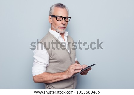 Modern technology leadership people concept. Half-turned portrait of authoritative respectful proud leader man using digital gadget at workplace rolled-up shirt sleeves isolated on gray background #1013580466