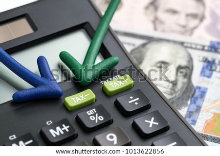 United States tax cuts, reform / reduce concept, arrows pointing to TAX minus button on calculator with background of blurred US Dollar banknotes, government offer tax deduction policy. #1013622856