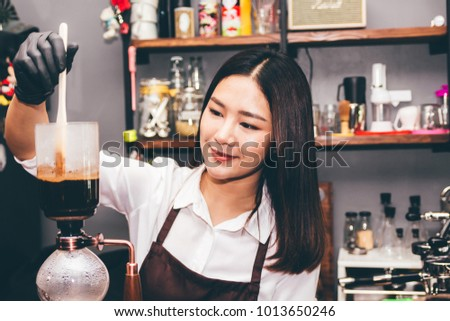 Women Barista making coffee on syphon coffee maker in the cafe #1013650246