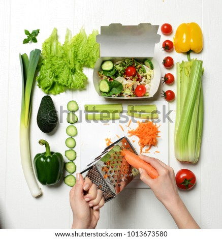 Top view of hands prepare light healthy eating dinner salad  with ingredients carrot, celery, tomatoes, green pepper paprika. Diet organic food preparation #1013673580