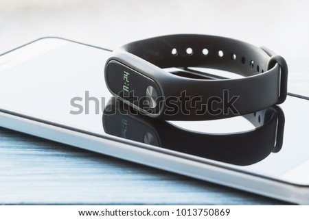 Black fitness watch (activity tracker) on the smartphone. Closeup, selective focus #1013750869