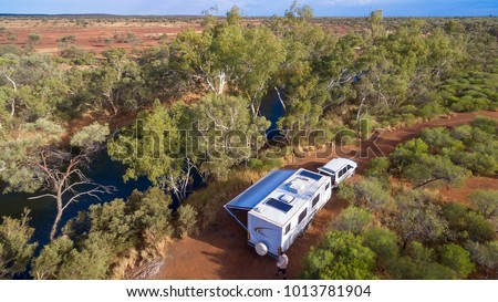 Aerial view of caravan and four wheel drive vehicle camped next to a river pool in the outback of Australia #1013781904
