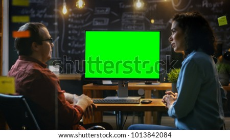 Beautiful Female Office Employee at Her Desk Talks with Her Male Coworker on the Desk Stands Computer with Mock-up Green Screen. Creative Evening Office. #1013842084