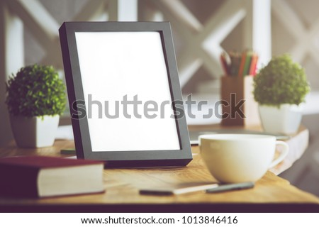 Close up of blank picture frame placed on office desk with coffee cup, supplies and other items on blurry background. Mock up