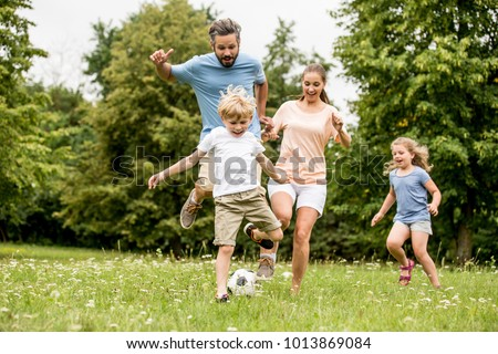 Active family play soccer in their leisure time Royalty-Free Stock Photo #1013869084