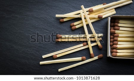 Matches in box, dark background. Macro photography. Close-up shot. Matches in open match-box on carton underlay.  Royalty-Free Stock Photo #1013871628