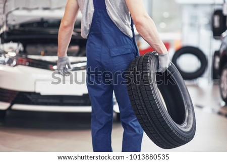 Mechanic holding a tire tire at the repair garage. replacement of winter and summer tires. #1013880535