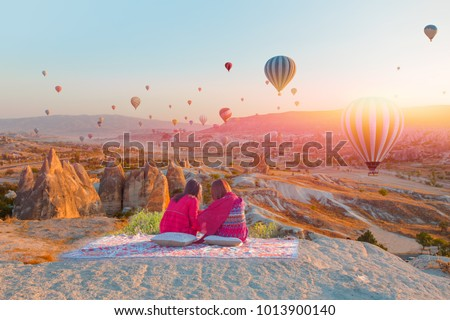 Hot air balloon flying over spectacular Cappadocia - Girls watching hot air balloon at the hill of Cappadocia #1013900140