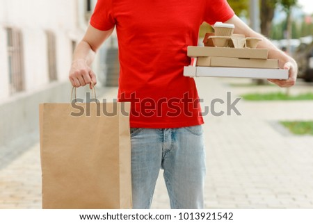 Cropped photo of a man holding a paper bag and food boxes with pizza, coffee and burgers. Delivery service concept. #1013921542