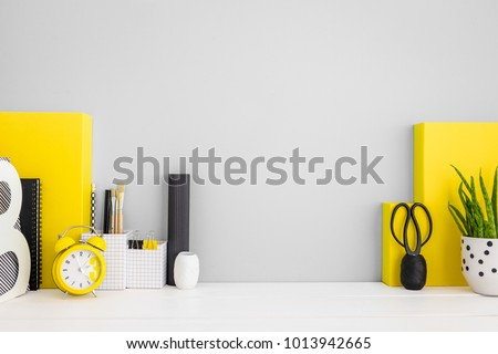 Stylish home office desk with copy space, cactus, statuette, books, and yellow office supplies. Mock up poster frame.  #1013942665