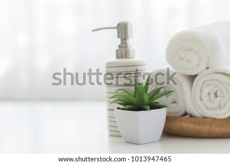 Ceramic soap, shampoo bottles and white cotton towels on white counter table inside a bright bathroom background. #1013947465