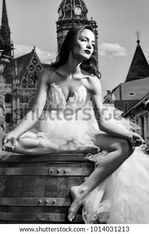 young sexy girl with brunette hair and red lips on pretty face in white wedding bride dress sitting on wooden barrel posing near church castle or palace building sunny outdoor on blue sky background #1014031213