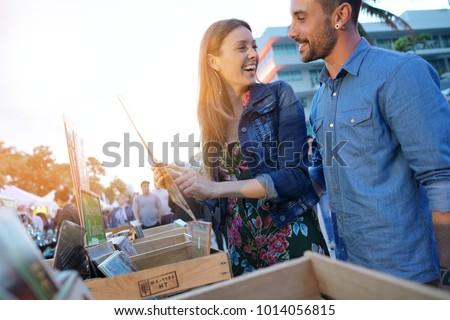 Couple walking by flea market in late afternoon