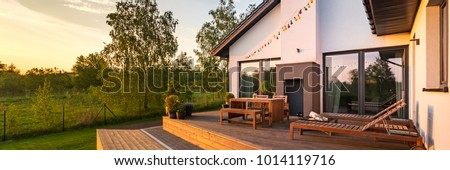 Modern house with patio and functional outdoor furniture, panorama