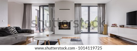 White, elegant living room with fireplace, tv, coffee table and couch, panorama Royalty-Free Stock Photo #1014119725