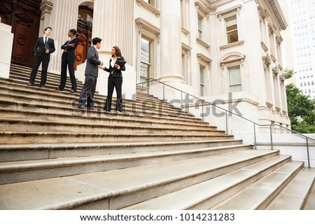 Four well dressed professionals in discussion on the exterior steps of a building. Could be lawyers, government workers, business people etc. #1014231283