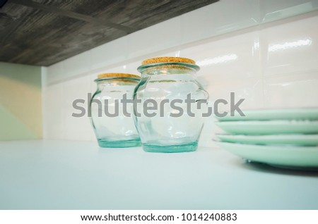 Empty glass containers on the kitchen shelf. #1014240883