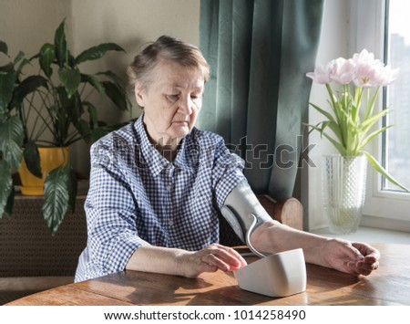 A retired woman sits near a window at a table and measures blood pressure #1014258490