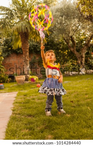 Portrait child dressed as a cowgirl playing with a big colorful ball in the garden. Happiness. Autumn #1014284440