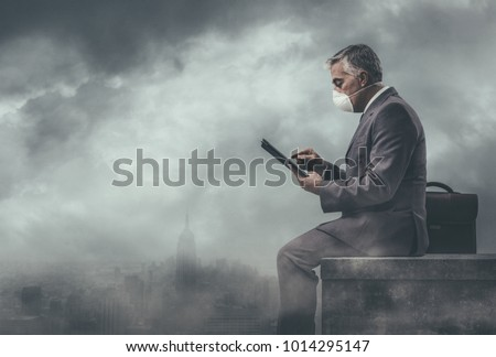 Businessman sitting on a rooftop in a polluted city and using a tablet: environmental pollution and business concept Royalty-Free Stock Photo #1014295147
