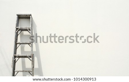aluminum foldable ladder and the shadow at white cement wall #1014300913