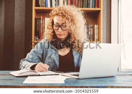 Blonde middle age business woman working at cafe, using laptop, smartphone, technology.