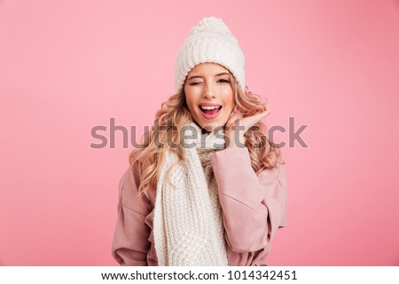 Image of happy young woman standing isolated over pink background wearing warm scarf. Looking camera. #1014342451